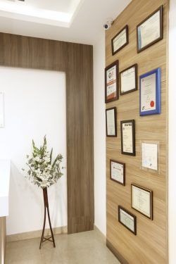 Awards and certificates placed in the wall of the dental care in coimbatore